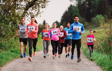 Large Group Of Multi Generation People Running A Race Competition In Nature.