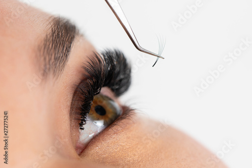 Pinturas sobre lienzo  The master builds up large colored eyelashes to the client