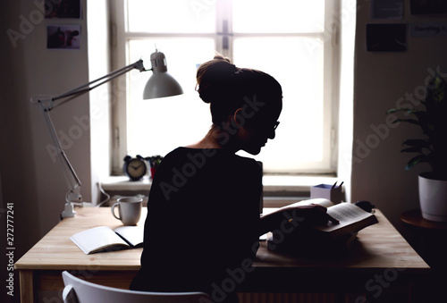 Fotografia A rear view of young female student sitting at the table, studying