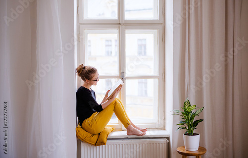 Valokuvatapetti A young female student with a book sitting on window sill, studying