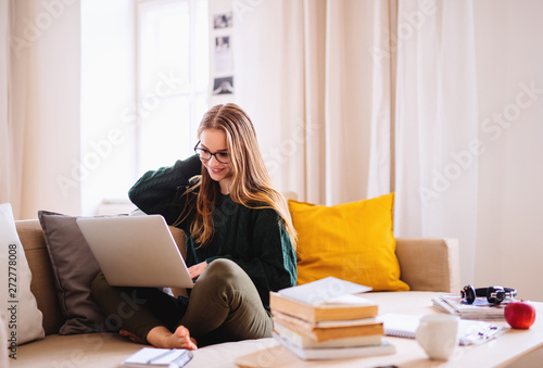 Obraz A young female student sitting on sofa, using laptop when studying. - fototapety do salonu