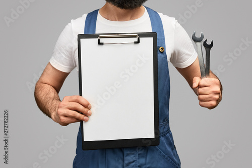 Crop technician with clipboard and wrenches