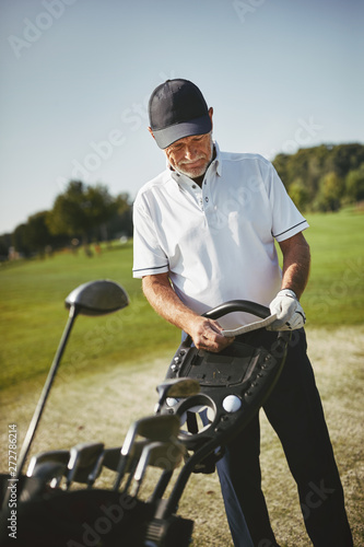 In de dag Eigen foto Senior man checking his scorecard while playing golf