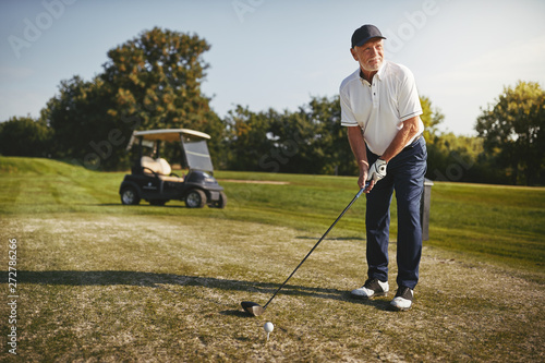 Photo sur Toile Kiev Senior man teeing up his shot on a golf course