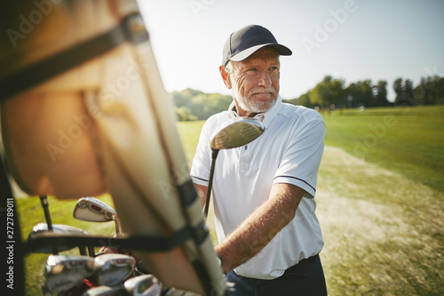 Senior man preparing to play golf on a sunny day