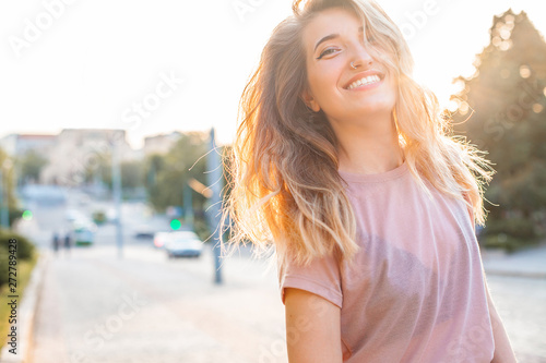 Happy young woman walking in the city,