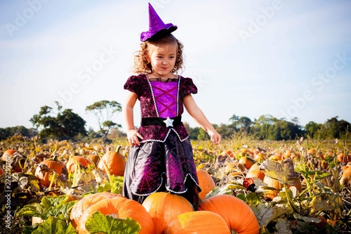 Fotografia Happy Halloween! Cute cheerful little witch with a magic wand