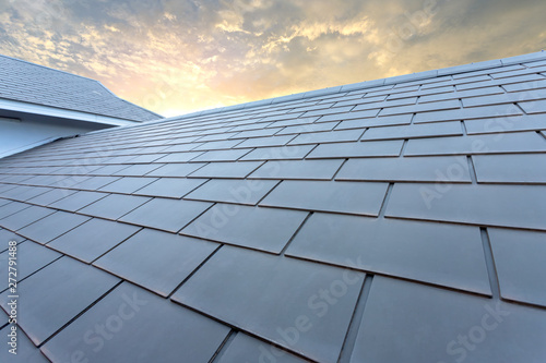 Obraz Slate roof against blue sky, Gray tile roof of construction house with blue sky and cloud of the sunset background - fototapety do salonu
