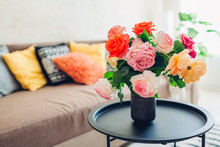 Interior Of Living Room Decorated With Flowers On Coffee Table And Cozy Couch With Cushions. Fresh Roses