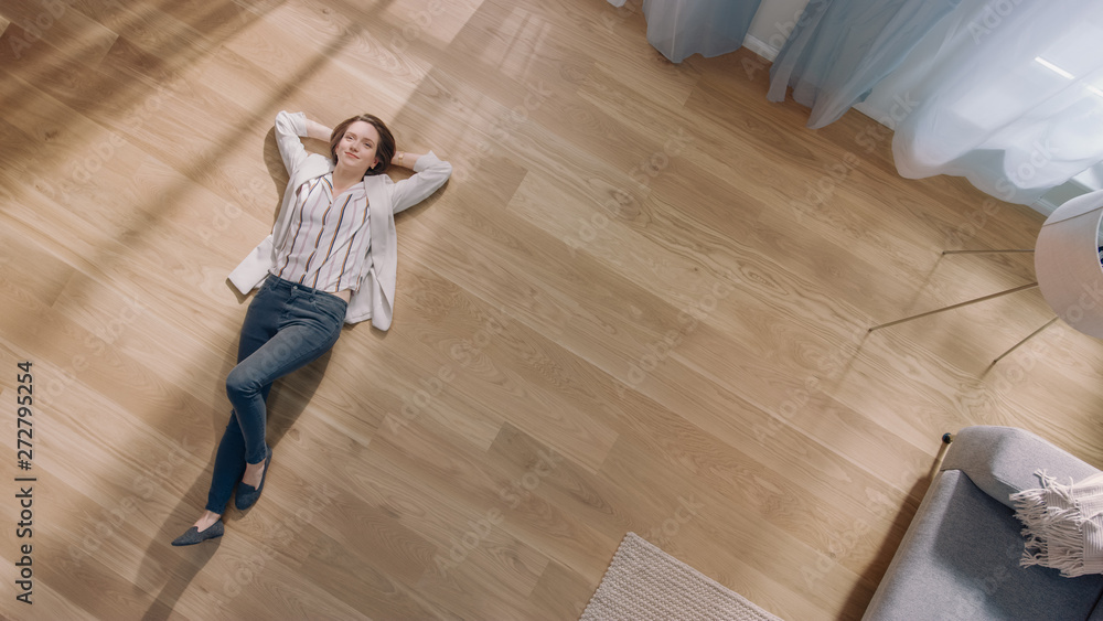 Fototapety, obrazy: Young Woman is Lying on a Wooden Flooring in an Apartment. She's Dressed Casually. Cozy Living Room with Modern Minimalistic Interior and Wooden Parquet. Top View Camera Shot.