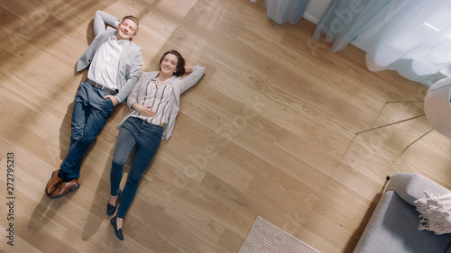 Photographie  Young Couple are Lying on a Wooden Flooring in an Apartment