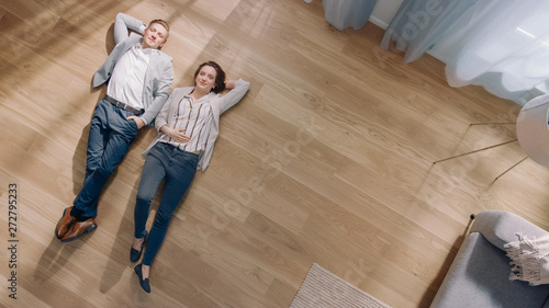 Fotografie, Obraz Young Couple are Lying on a Wooden Flooring in an Apartment