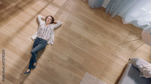 Fotografie, Obraz  Young Woman is Lying on a Wooden Flooring in an Apartment