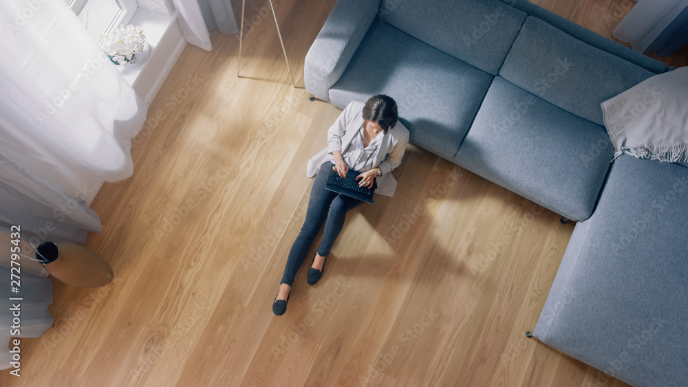 Fototapety, obrazy: Young Woman is Sitting on a Floor, Working or Studying on a Laptop. Cozy Living Room with Modern Interior, Grey Sofa and Wooden Flooring. Top View Camera Shot.