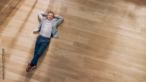 Photo sur Toile Kiev Young Man is Lying on a Wooden Flooring in an Apartment. He's Wearing a Jacket and White Shirt. Cozy Living Room with Modern Minimalistic Interior and Wooden Parquet. Top View Camera Shot.