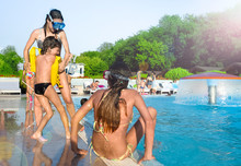Group Of Happy Children Playing On The Swimming Pool In Aqua Park At The Day Time. People Having Fun Outdoors. Concept Of Friendly Family And Summer Vacation.
