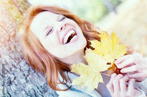 Valokuva  lachende rothaarige Frau mit Herbstblättern