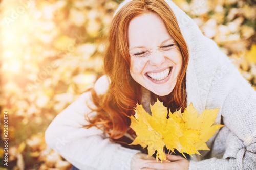 Portrait einer freundlichen Rothaarigen Frau im Herbst mit Ahornblättern Canvas-taulu