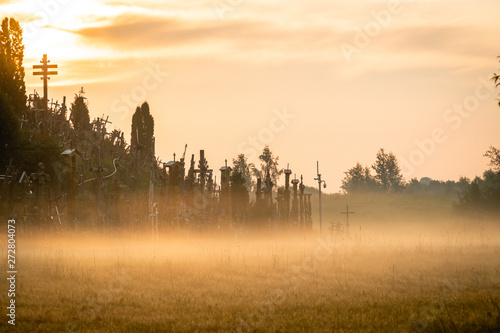 Poster Morning with fog Bunch of wooden crosses during summer sunrise Hill of Crosses is a site of pilgrimage.