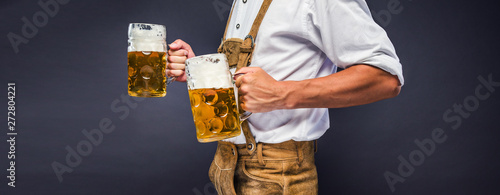 Fotografering Man in traditional bavarian clothes holding mug of beer