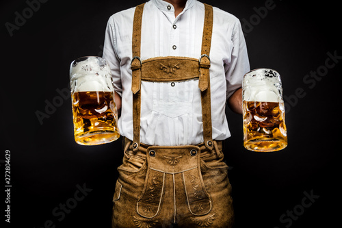 Billede på lærred Man in traditional bavarian clothes holding mug of beer