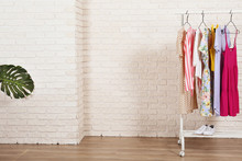 Women's Hip Clothing Store Interior Concept. Row Of Different Colorful Female Clothes Hanging On Rack In Hipster Fashion Show Room In Shopping Mall. White Brick Wall Background. Copy Space.