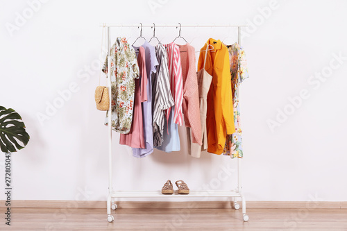 Obraz Women's hip clothing store interior concept. Row of different colorful female clothes hanging on rack in hipster fashion show room in shopping mall. White wall background. Copy space. - fototapety do salonu