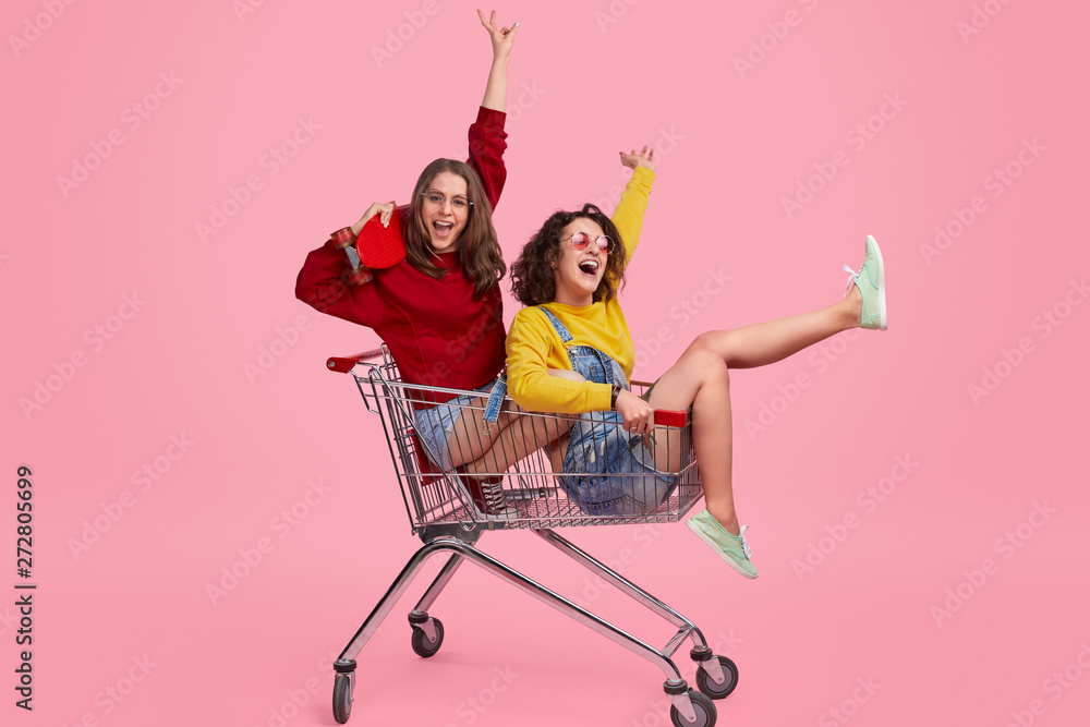 Fototapeta Cheerful sisters riding shopping trolley