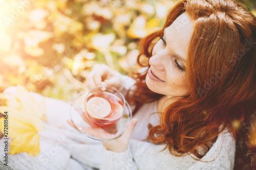Valokuva  Portrait einer rothaarigen Frau im Herbst mit Blättern mit Teeglas trinkt Tee