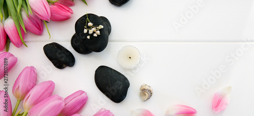 Printed kitchen splashbacks Tulip Spa setting with tulips , black stones and candle on white wood background.