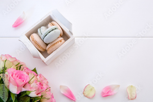 Foto auf Gartenposter Macarons Pink roses and macaron cookies in the basket on white background.
