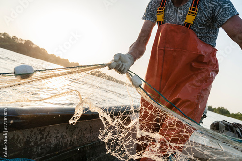 Fototapeta Dynamic composition with a fisherman dressed in an orange rompers gathering his trammel net during a fishing trip on the Danube river