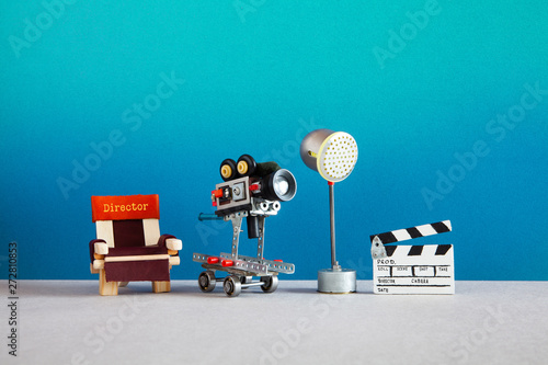 Photographie Motion picture backstage area with director's chair, camera or camcorder on wheels, the lighting projector spotlight and clapperboard
