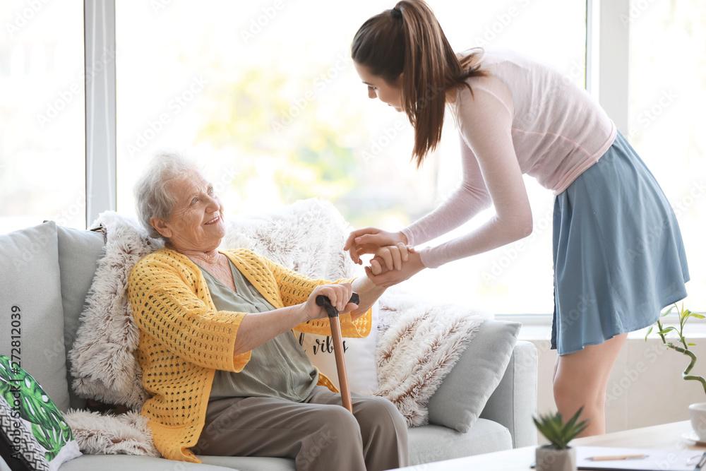 Fototapeta Caregiver with senior woman in nursing home