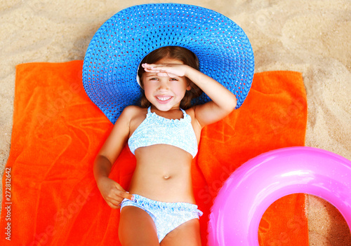 Valokuva Summer portrait little girl in bikini, straw hat lying sunbathing on sand beach