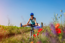 Happy Young Woman Cyclist Riding A Mountain Bicycle In Summer Field. Girl Having Fun Lifting Legs