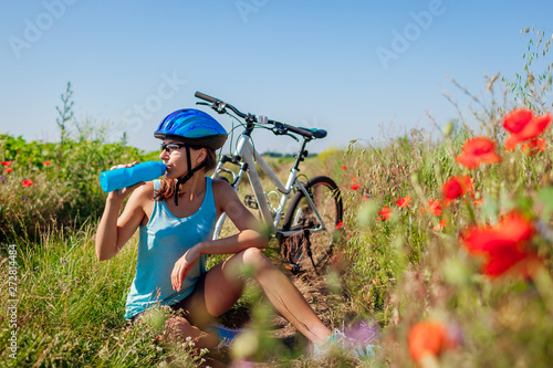 Happy young woman cyclist drinking water and having rest after riding bicycle in summer field Canvas Print