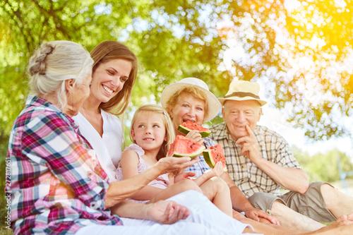 Fotografie, Obraz  Familie mit Kind beim Melone essen im Sommer