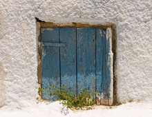 Old Window With Weathered Blue Shutters And White Plaster Wall.