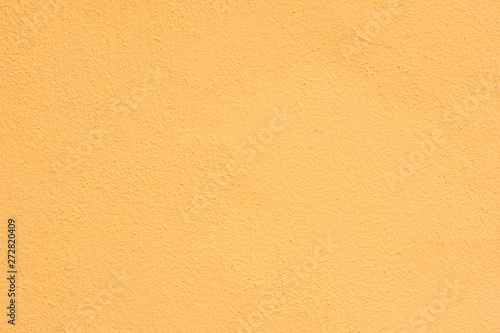 Fotografie, Obraz  Background of a yellow stucco coated and painted exterior, rough cast of cement