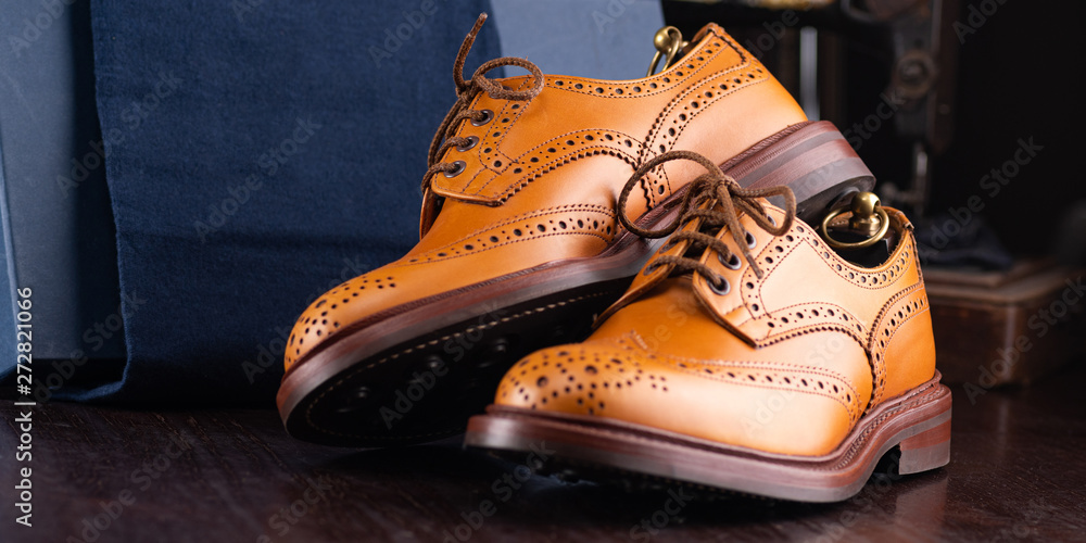 Fototapeta Brown full grain leather brogues on wooden display in in men shoes boutique store with box and cloth shoe bags.