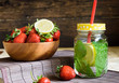 lemon water with mint and bowl with strawberries on a wooden table