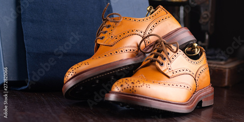 Pinturas sobre lienzo  Brown full grain leather brogues on wooden display in in men shoes boutique store with box and cloth shoe bags