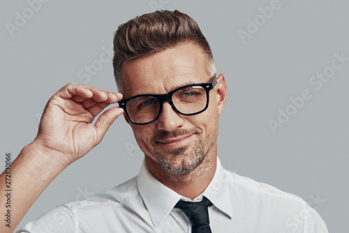 Handsome businessman. Good looking young man adjusting eyewear while standing against grey background
