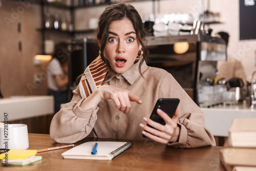 Fototapety, obrazy: Shocked young beautiful woman using mobile phone indoors in cafe.