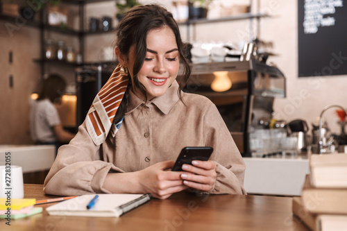 Fototapety, obrazy: Happy young beautiful woman using mobile phone indoors in cafe.