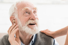 Glad Man With Hearing Aid In E...