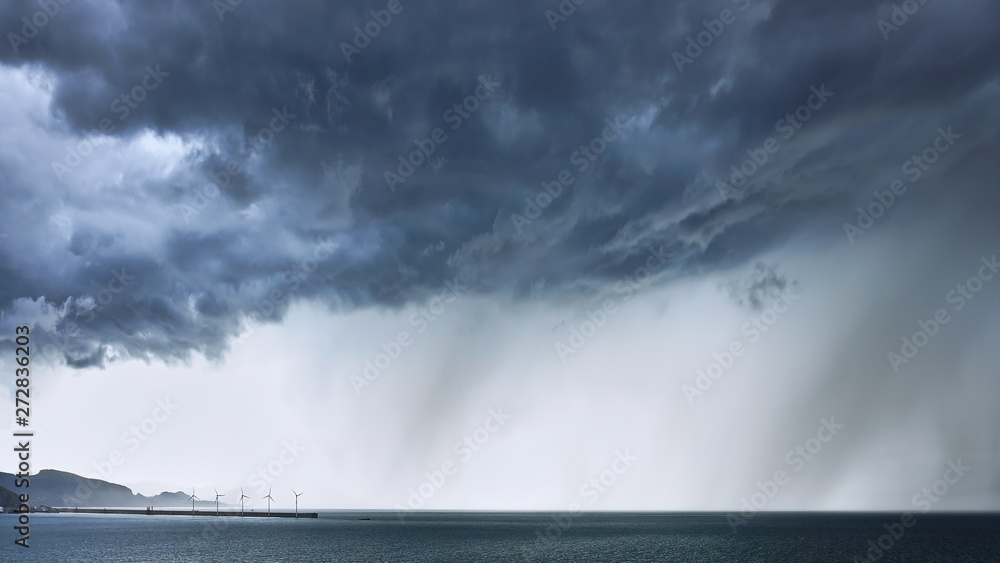 stormy clouds with rain on the sea