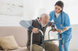 canvas print picture - Doctor helping to retired man, getting up from sofa