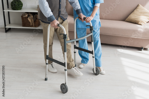 Foto Senior man walking with nurse, and recovering from injury